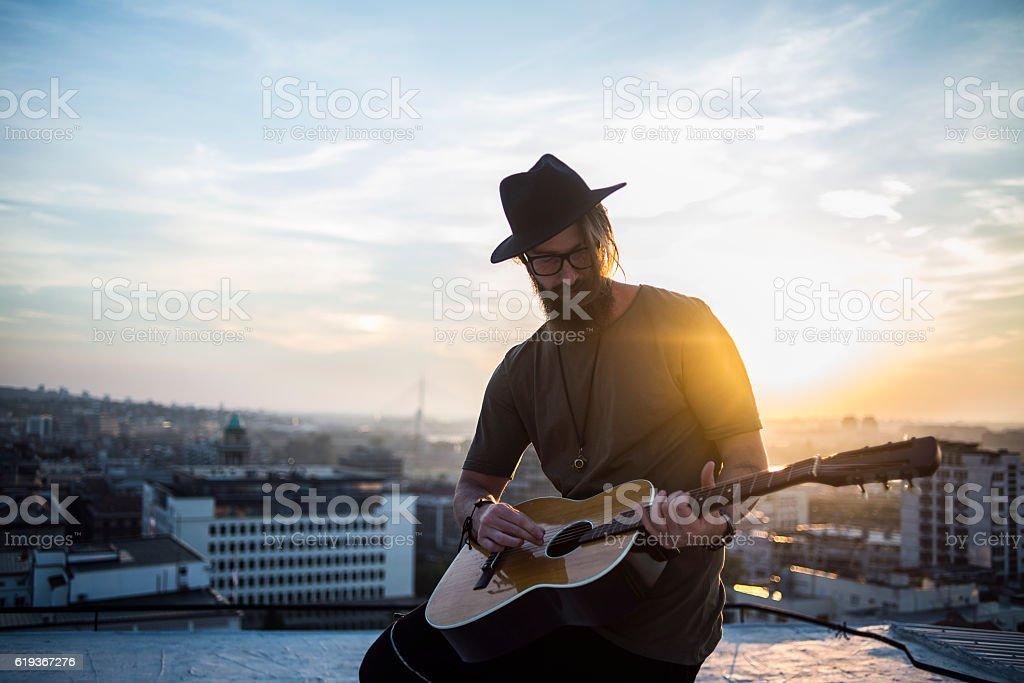 man playing the guitar on top of the city stock photo
