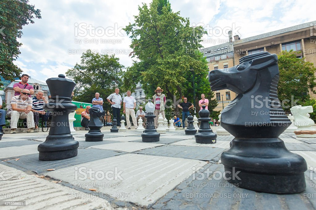 Man playing to an outdoor chess game stock photo