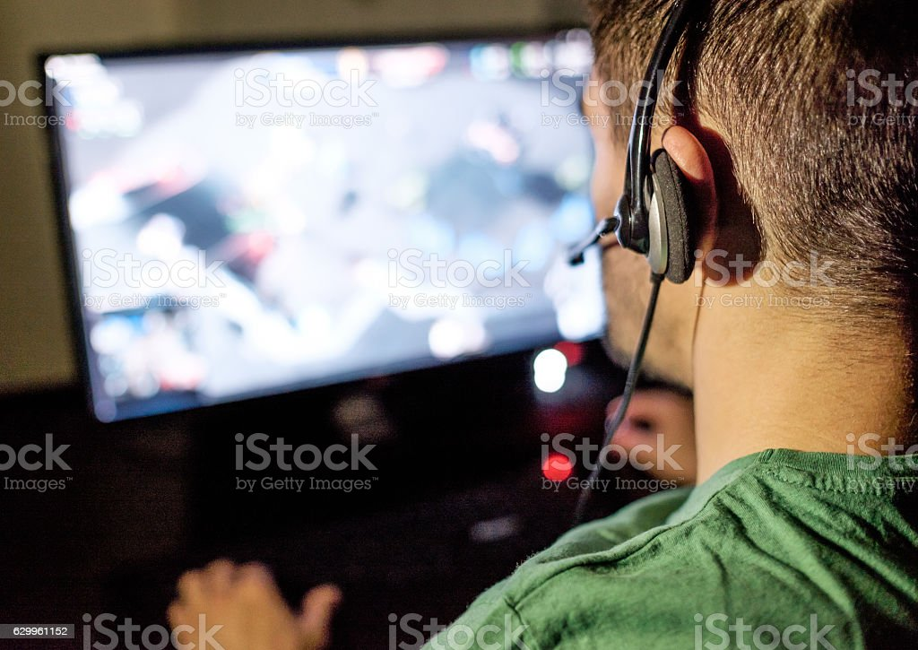 Man playing video game in dark room stock photo