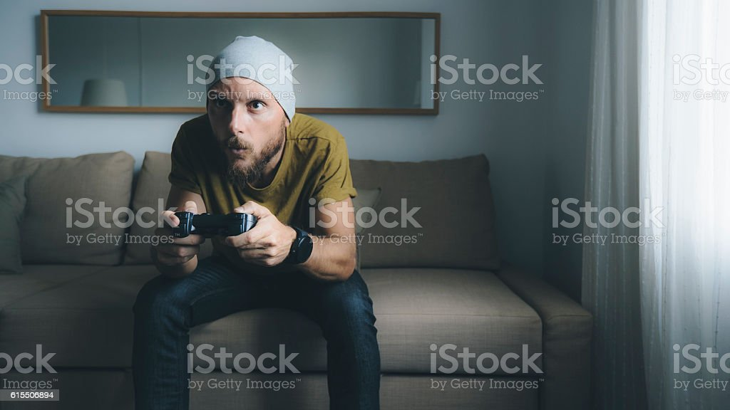 Man playing video games at home alone stock photo