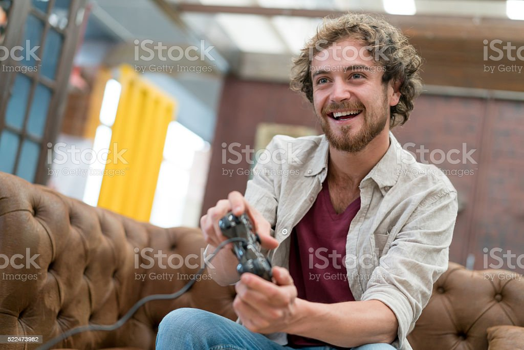 Man playing video games at the office stock photo