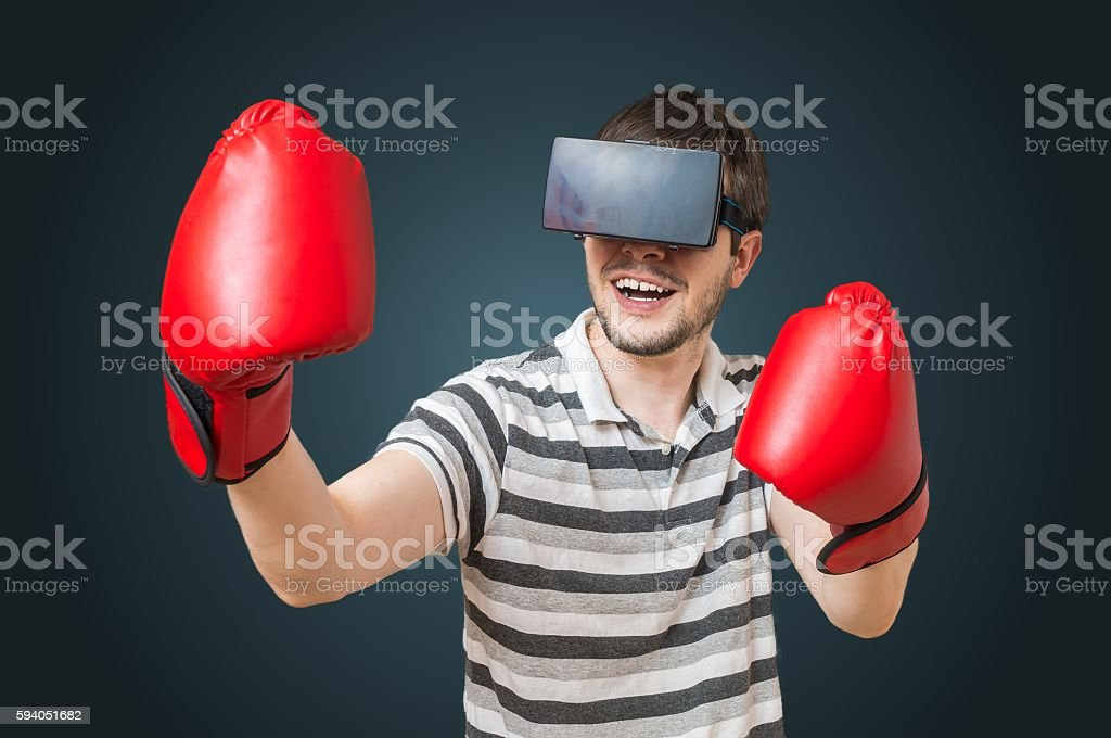 Man playing videogame and boxing with 3D virtual reality headset. stock photo