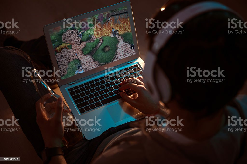 Man playing videogame on laptop stock photo