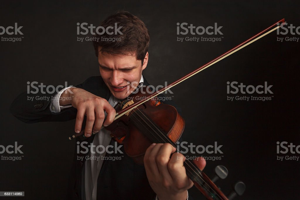 Man playing violin showing emotions and expressions stock photo