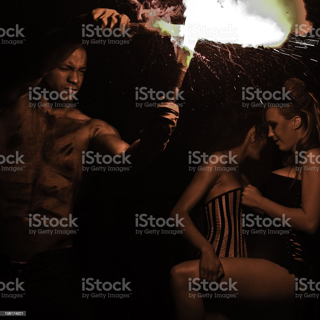 Man Playing with Flares and Women Flirting in Background royalty-free stock photo