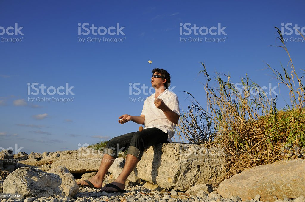 Man playing with stones stock photo
