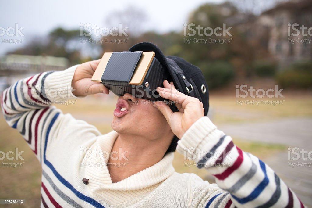 Man playing with virtual reality simulator at park stock photo