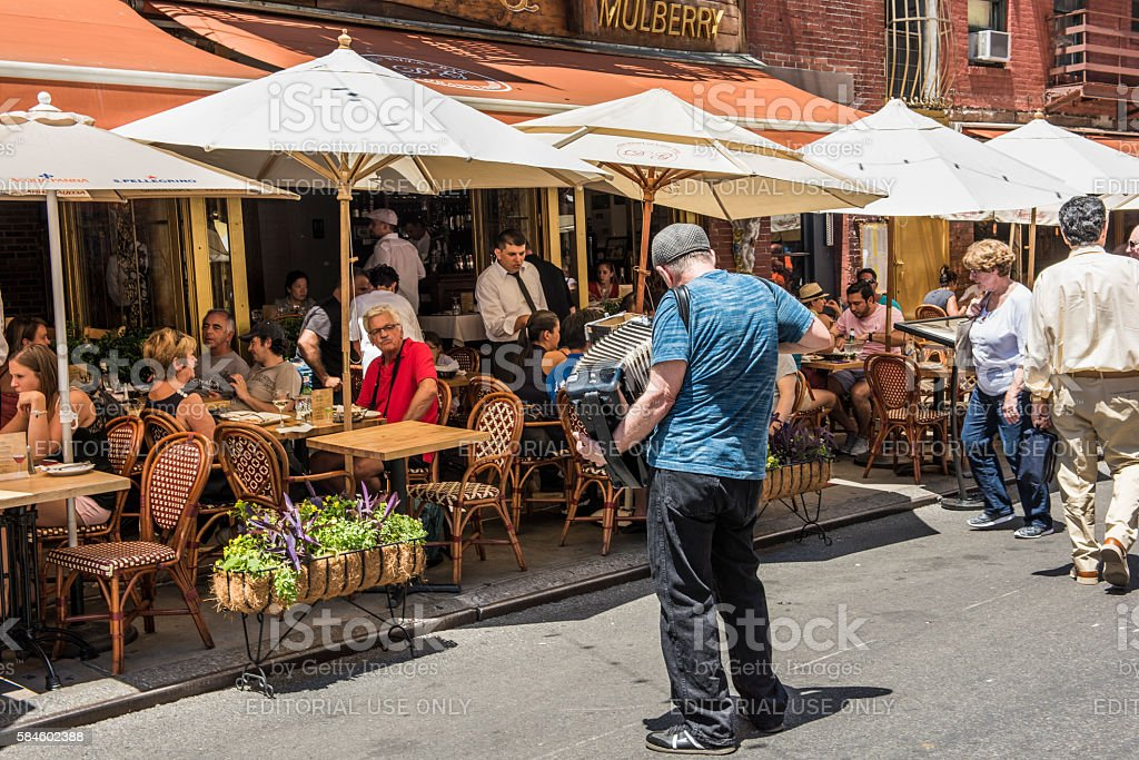 Man plays accordian by restaurant in Little Italy stock photo