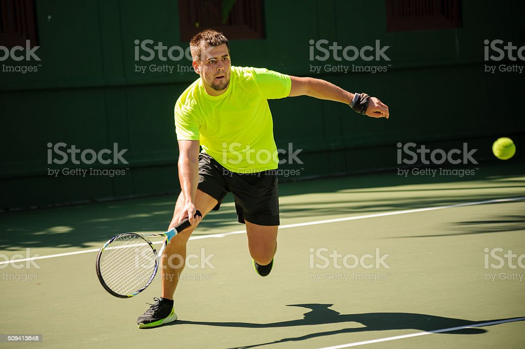 Man plays tennis in bright cloth stock photo