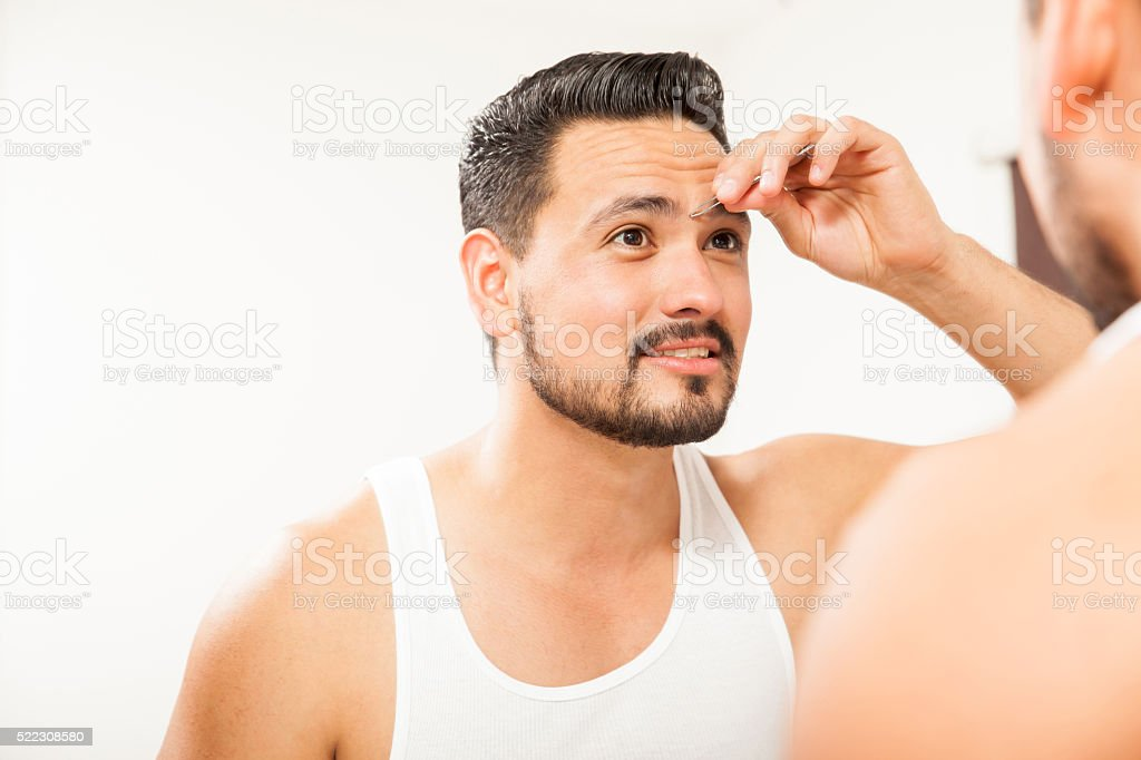 Man plucking his eyebrows in the bathroom stock photo