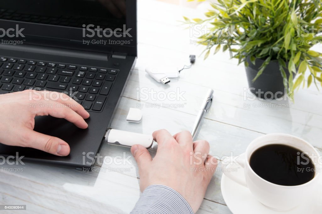 Man plugging GSM modem into a laptop stock photo