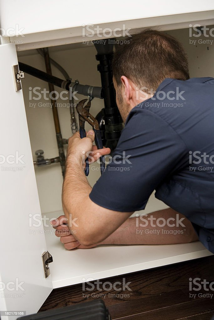 Man Plumber Working in Kitchen Happy with Uniform and Tools royalty-free stock photo