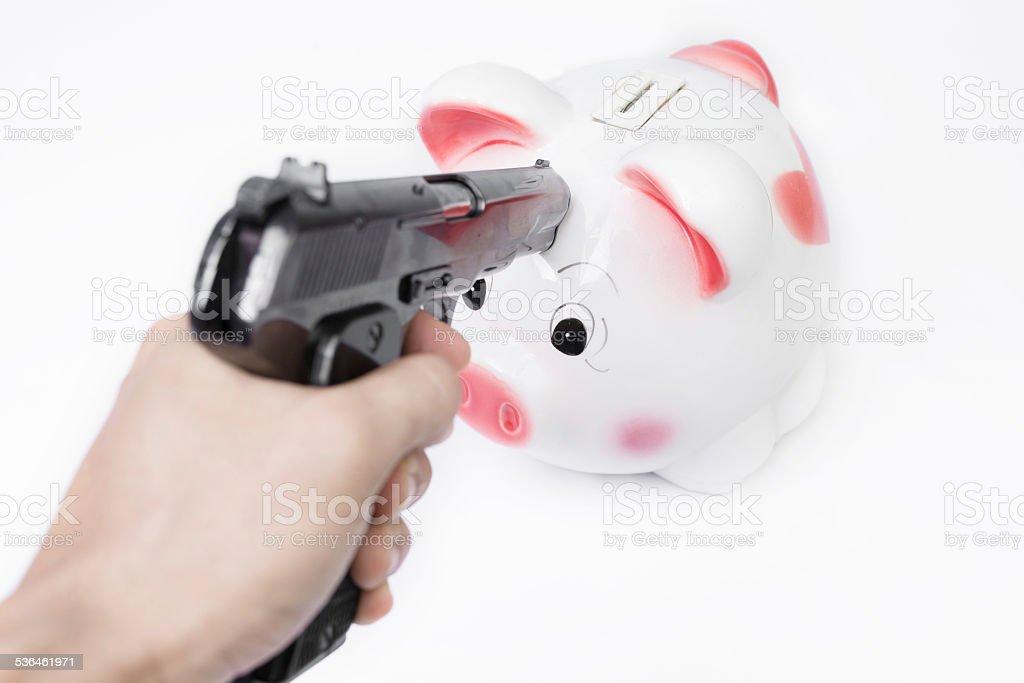 Man pointing a gun at a piggy bank stock photo