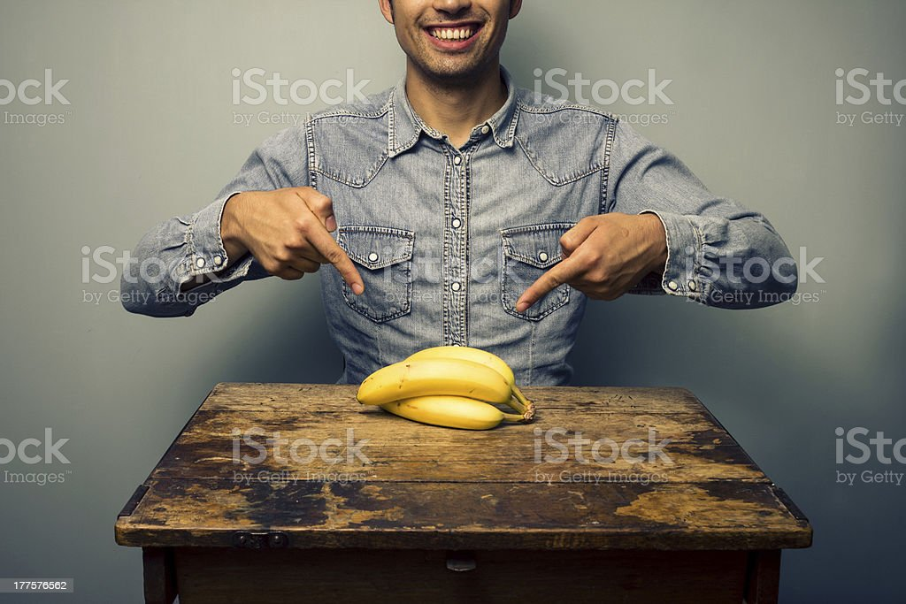Man pointing at bananas on old desk royalty-free stock photo