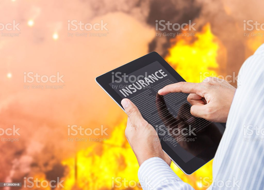 Man pointing at insurance wording on tablet with fire background stock photo