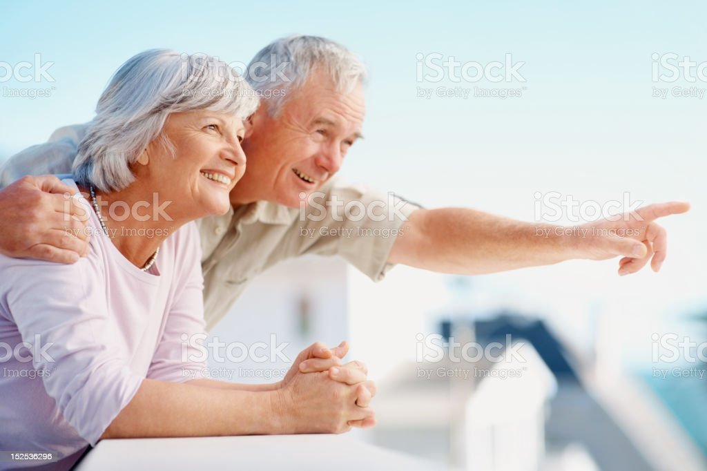 Man pointing out something to wife while standing at balcony royalty-free stock photo