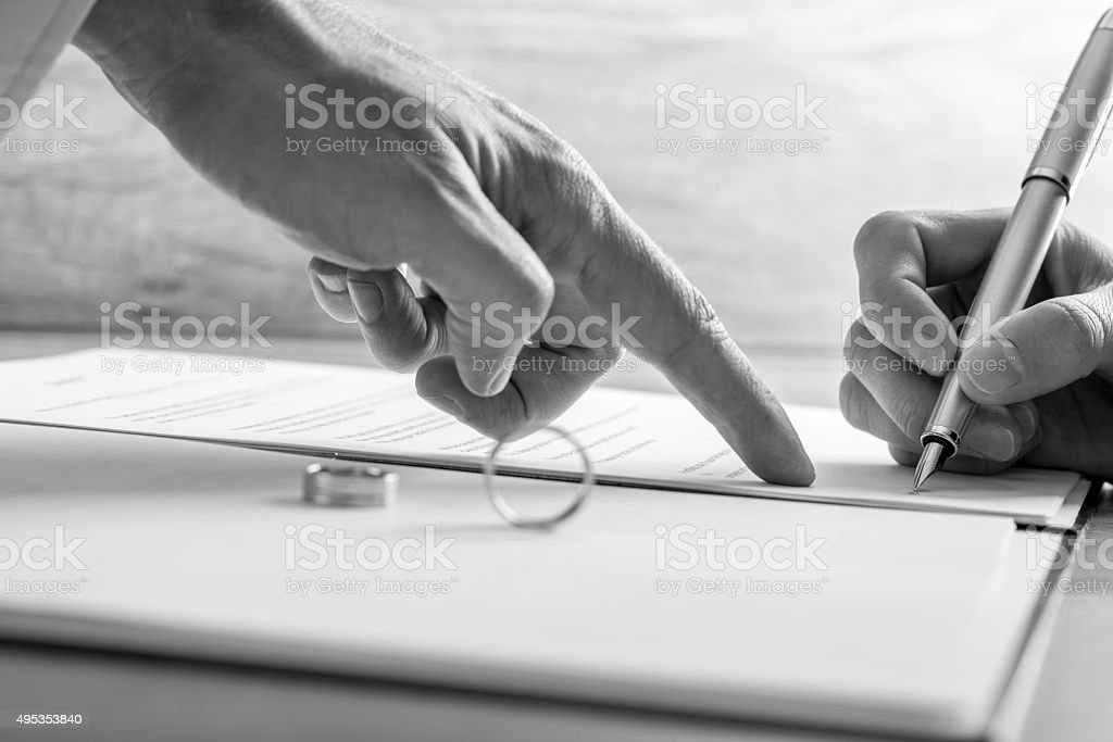 Man pointing to a woman where to sign divorce papers stock photo