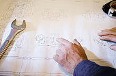 Man pointing to blueprint in industrial manufacturing workshop