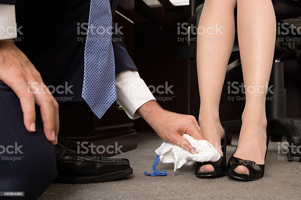 Man polishing businesswomans shoes stock photo