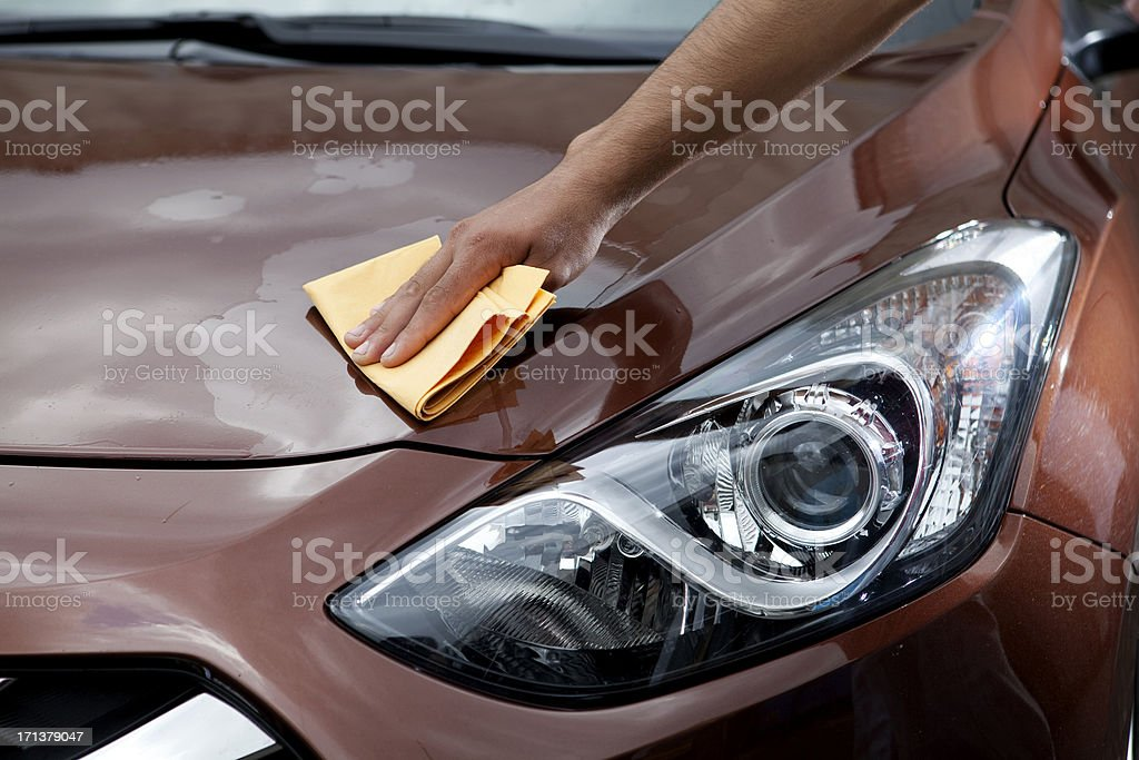 man polishing car hood stock photo