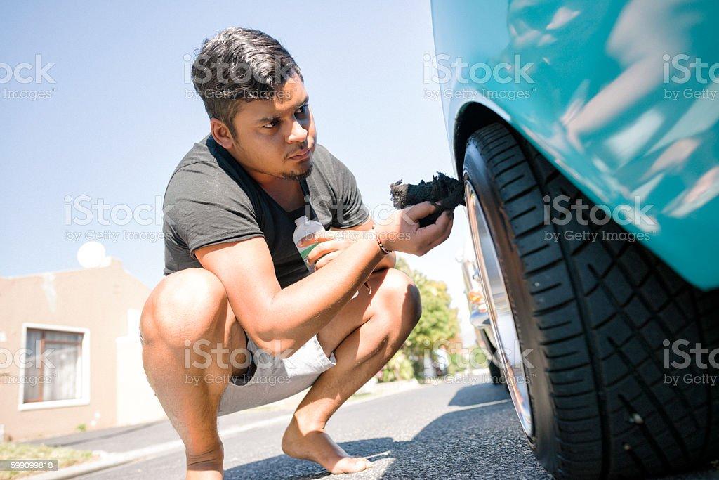 Man Polishing The Tyres Of His Vintage Car stock photo