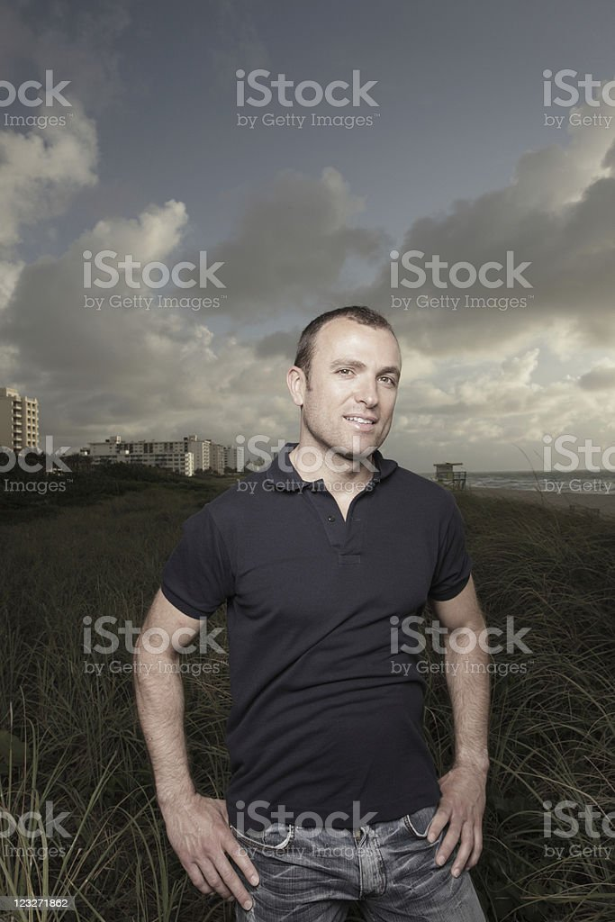 Man posing in a field of dunes royalty-free stock photo