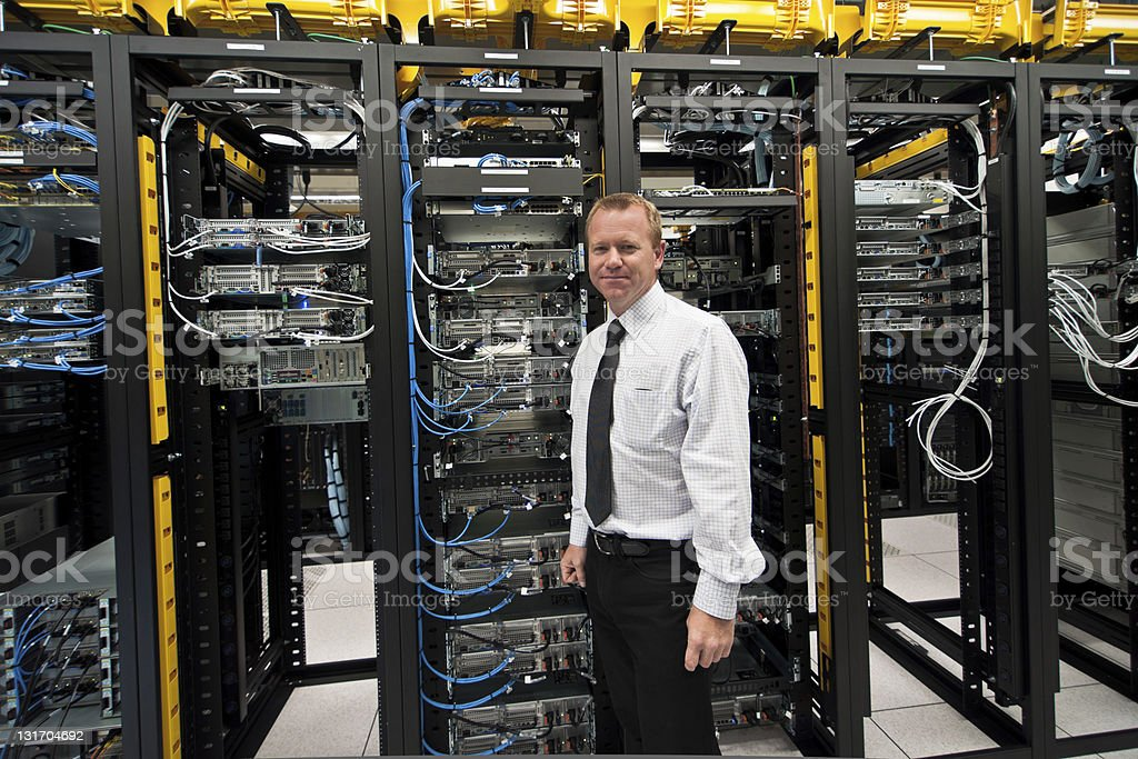 Man posing in front of datacenter equipment racks stock photo