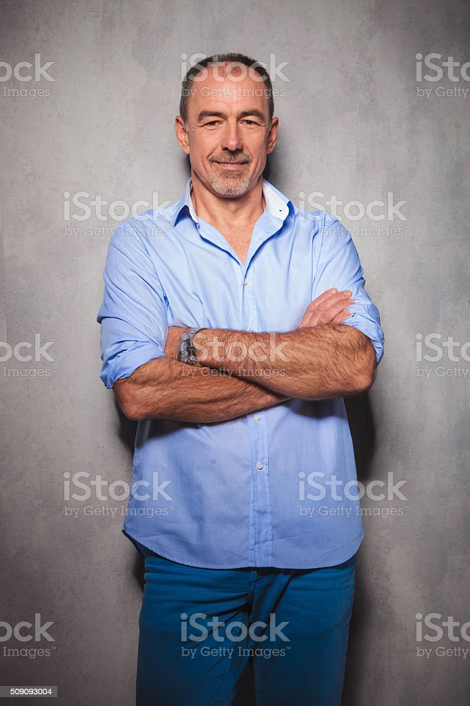 man posing in studio background with hands crossed stock photo