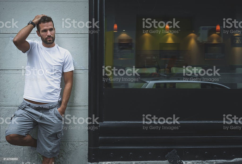 Man posing on a wall stock photo