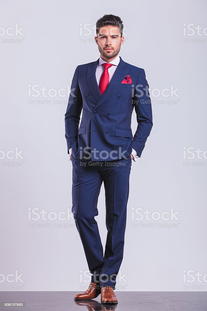 man posing on studio background with hands in pockets stock photo