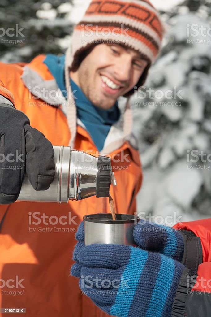 Man pouring a drink from a thermos stock photo