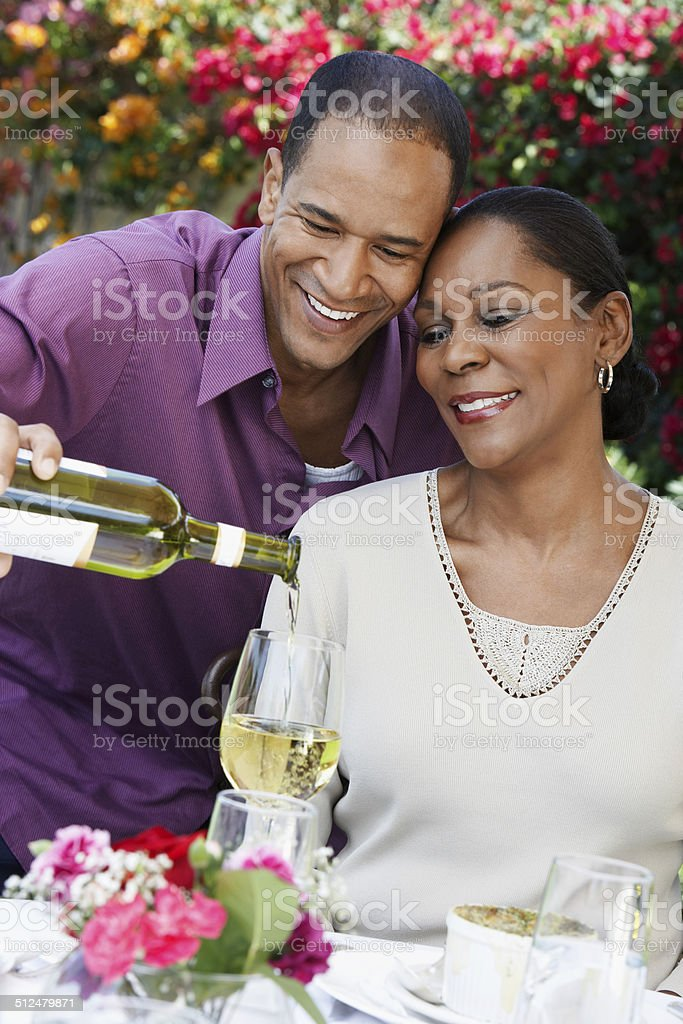 Man Pouring a Glass of Wine for His Wife stock photo