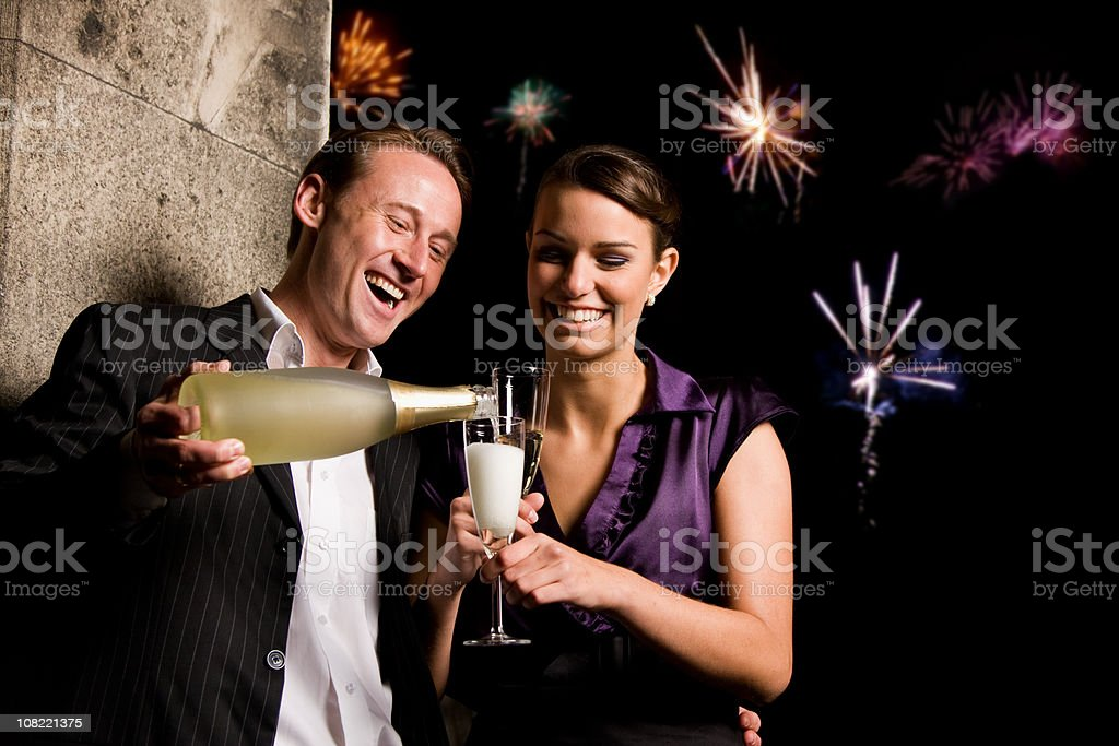 Man Pouring Champagne Into Woman's Glass at Party stock photo