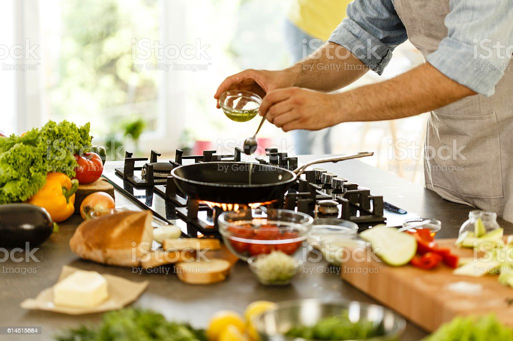 Man pouring cooking oil into frying pan stock photo