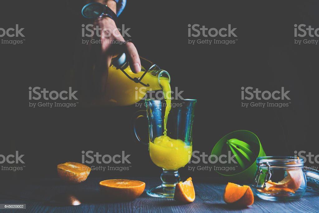 Man pouring fresh orange juice into a glass stock photo