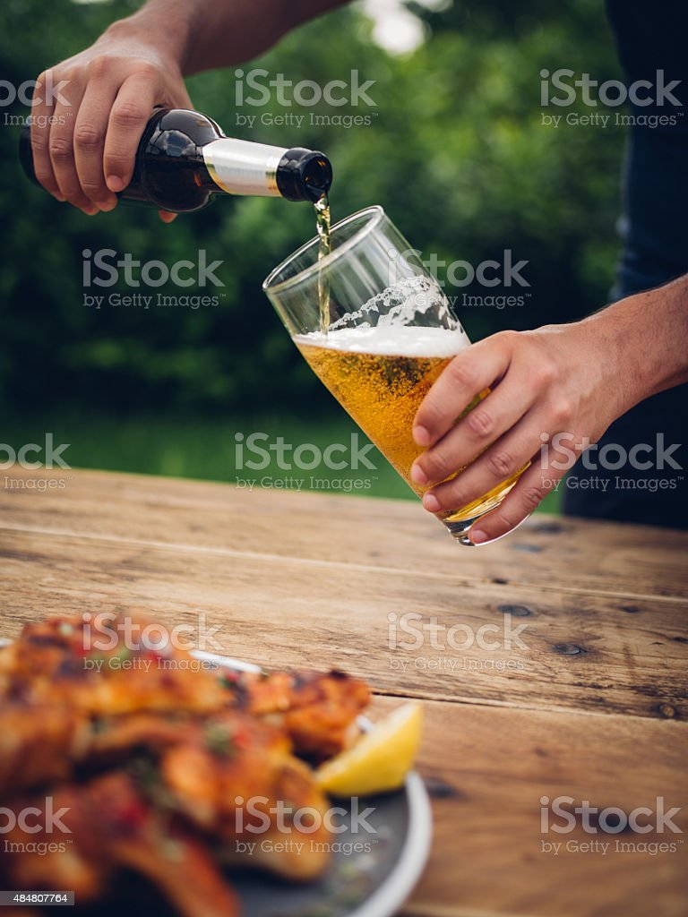 Man pouring glass of beer with chicken wings in foreground stock photo