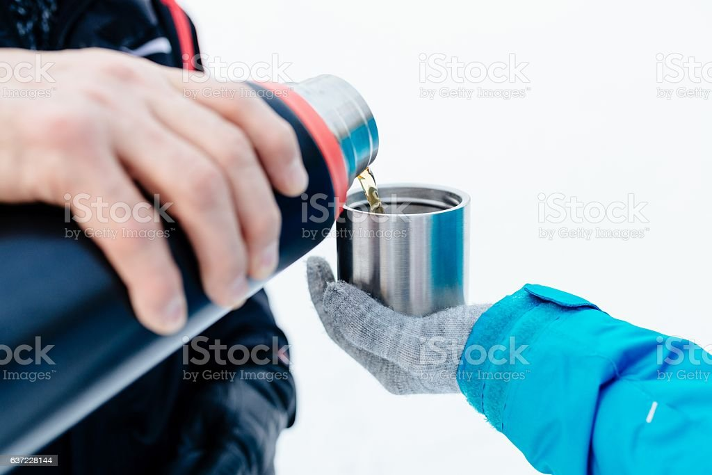 Man pouring hot tea from a thermos stock photo
