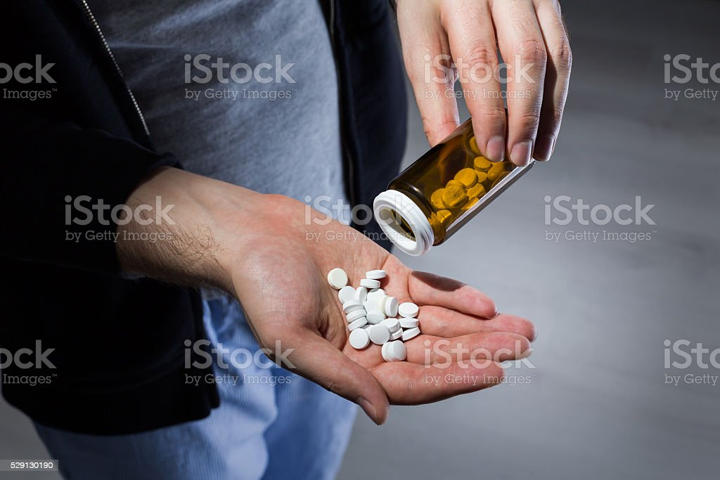 Man pouring pills stock photo