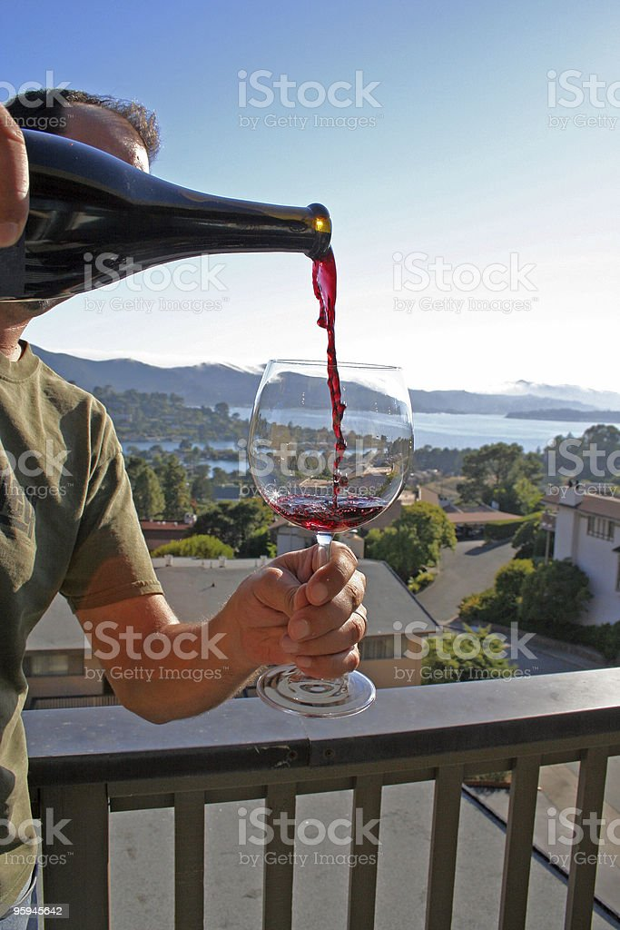 Man pouring red wine on scenic deck stock photo