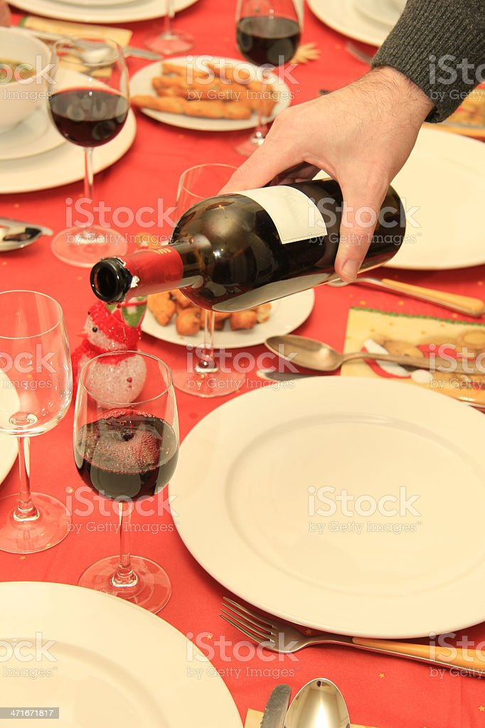 Man pouring wine at Christmas table royalty-free stock photo