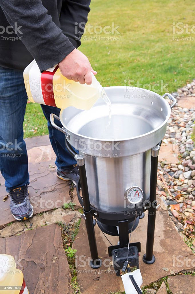 man pours oil into a large outdoor deep fryer royaltyfree stock photo - Outdoor Deep Fryer