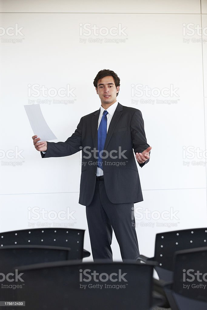 A man practicing his speech in front of empty chairs stock photo