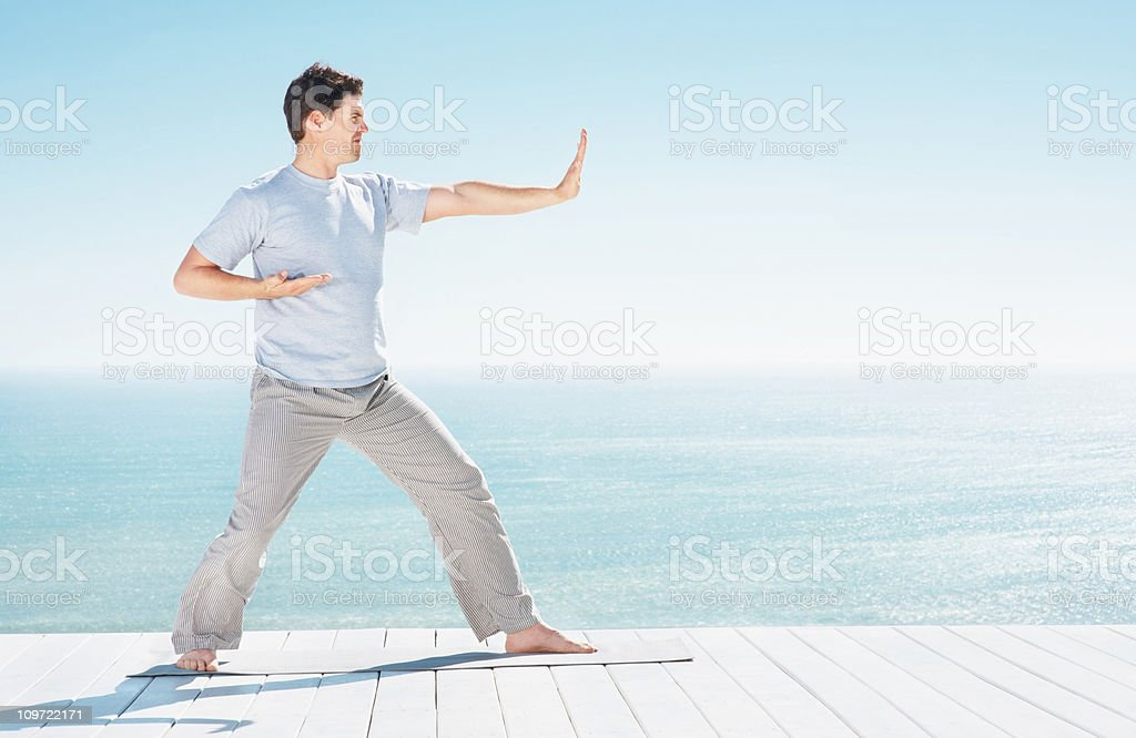 Man practicing martial arts by copyspace over peaceful sea royalty-free stock photo
