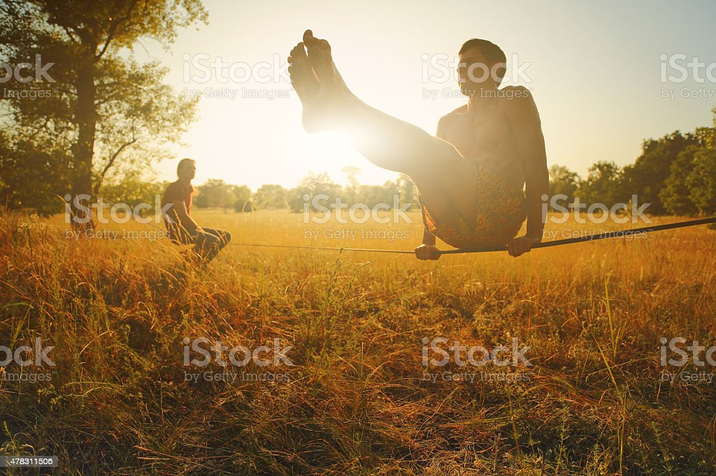 Man practicing on slackline in the meadow at sunset. stock photo