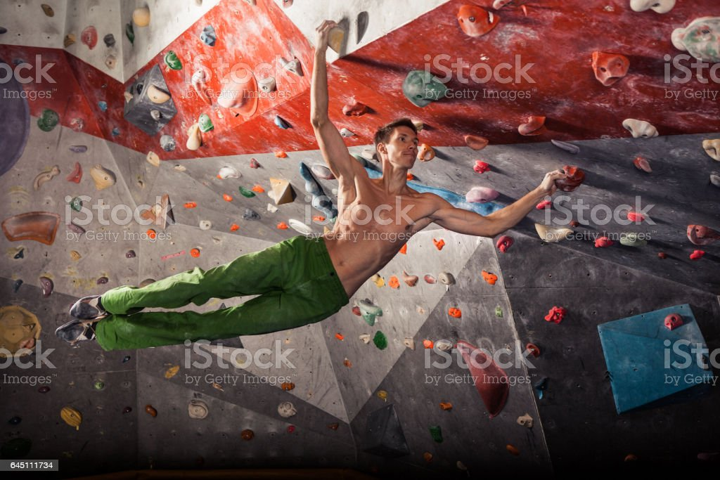 man practicing rock-climbing on a rock wall indoors stock photo