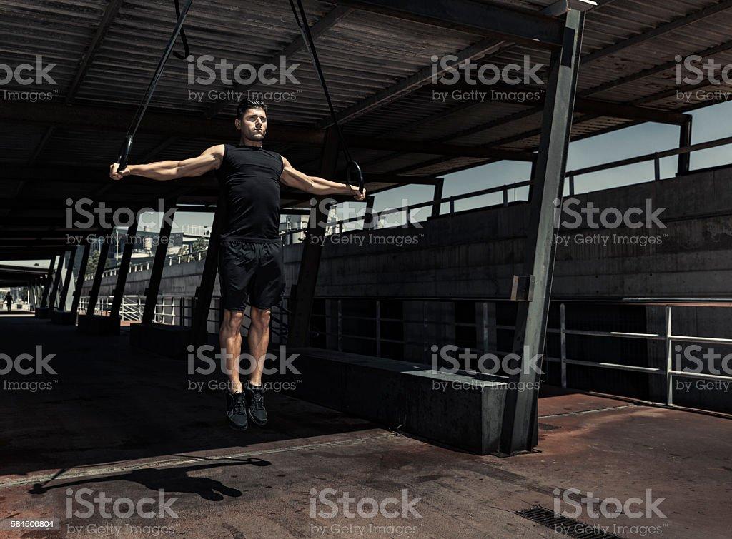 Man practicing urban calisthenics exercises stock photo