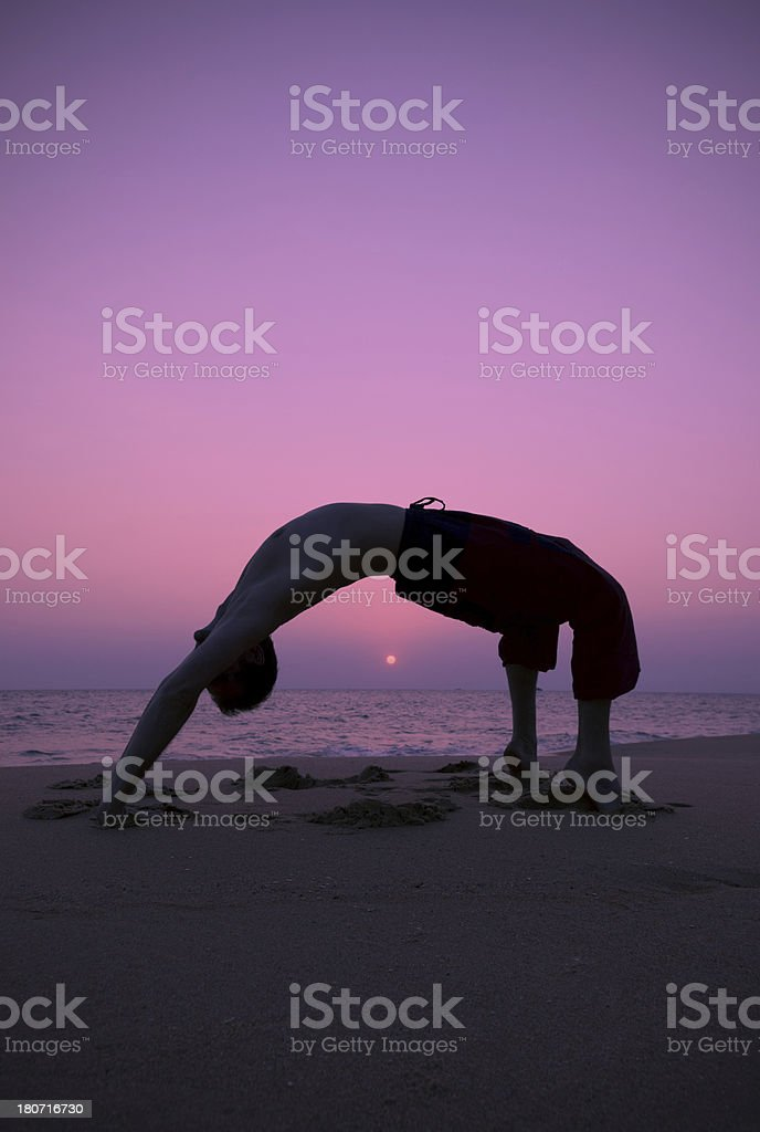 Man practicing yoga at sunset royalty-free stock photo
