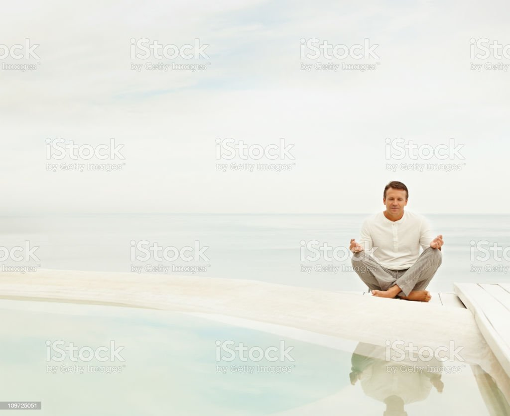Man practicing yoga in a lotus position by pool stock photo