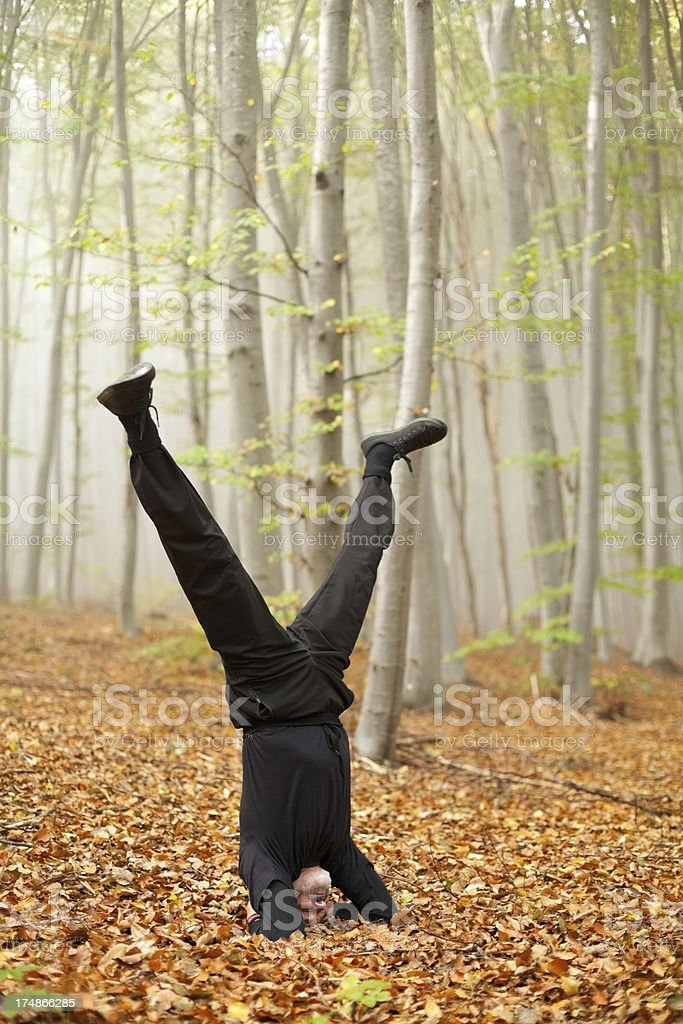 Man practicing yoga in the misty forest at autumn royalty-free stock photo