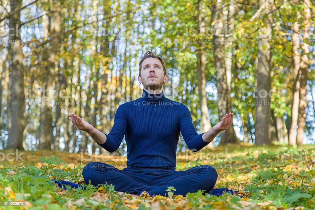 Man practicing yoga in the park atmosphere. Fallen yellow leaves. stock photo